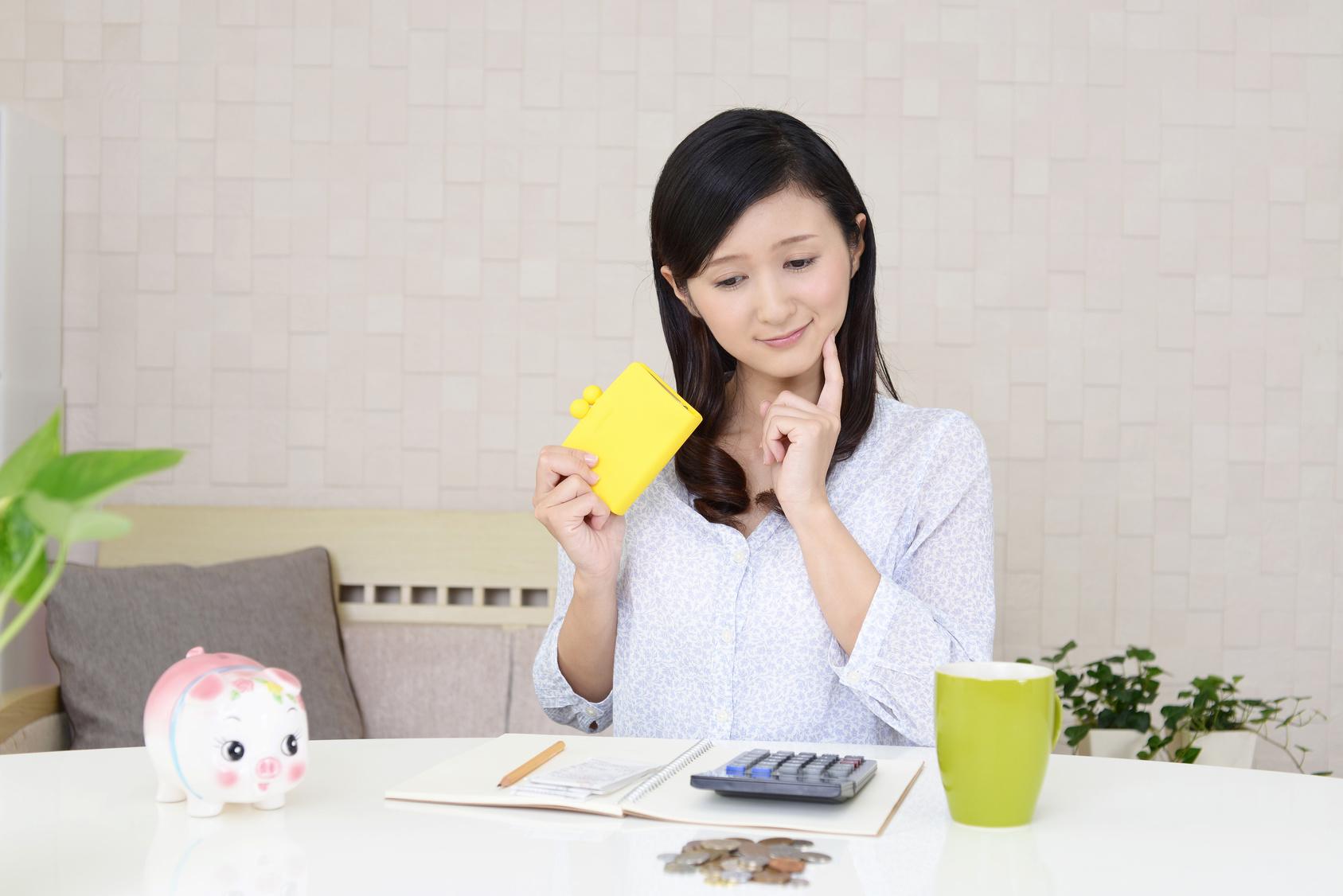 金・財布を持つ女性