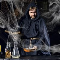 Halloween magician is preparing for a magical ritual in ancient table