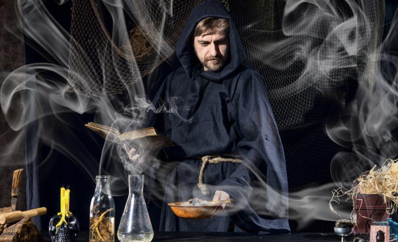 術・Halloween magician is preparing for a magical ritual in ancient table
