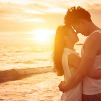 愛young couple kissing at sunset on beach