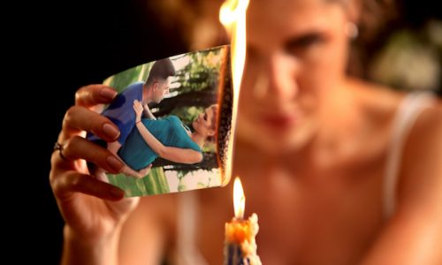 Broken heart woman. Couple break up. Burning family photo.