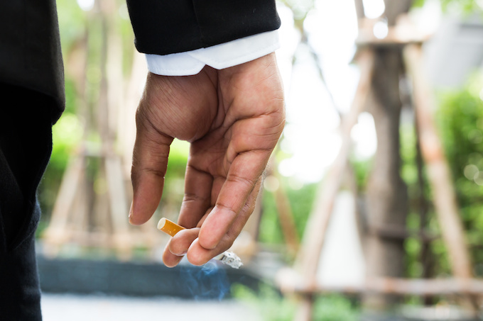 businessman smoking Cigarettes in hand in the parks.
