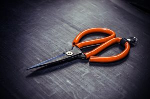 Orange scissors on work desk background.