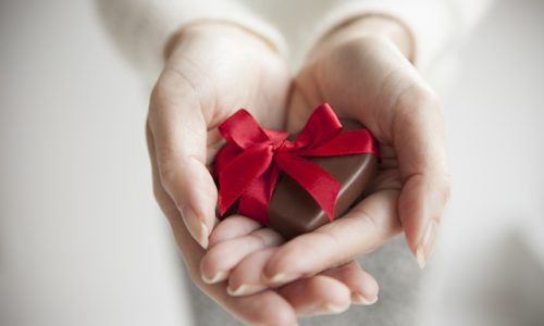 The woman presents a heart-shaped chocolate