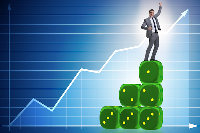 Businessman balancing on top of dice stack in uncertainty concep