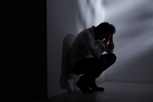 Abandoned man sitting beside wall