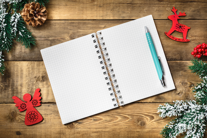 Blank paper notebook on brown wooden table background. Top view with copy space.