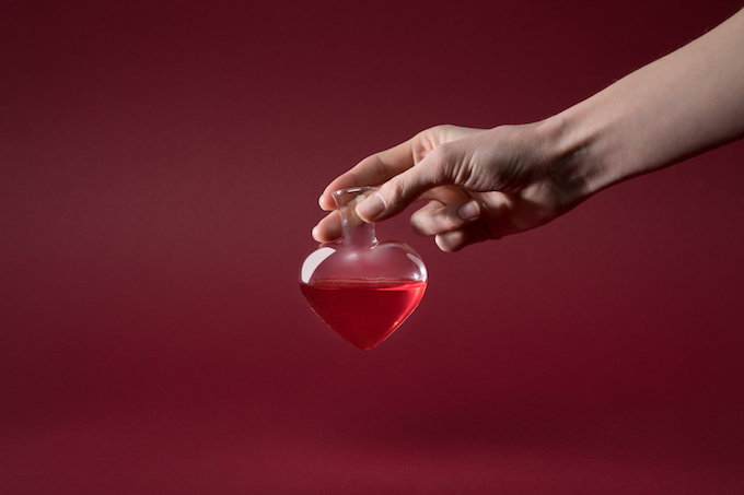 cropped image of woman holding heart shaped glass jar of love elixir isolated on red