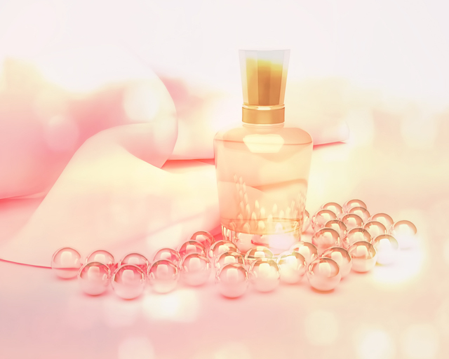 Perfume in a glass bottles and pearl beads on pink.