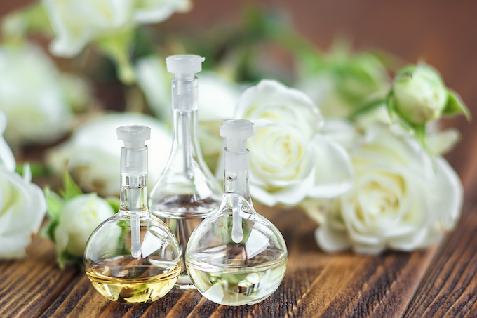 Essential oil in glass bottle with rose flowers on wooden background. Small bottles of perfume. Beauty treatment. Spa concept. Selective focus.