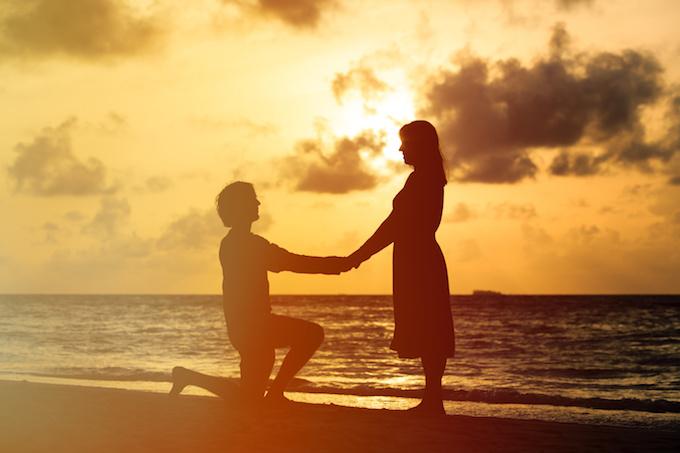 愛・Silhouette of a young romantic couple at sunset beach
