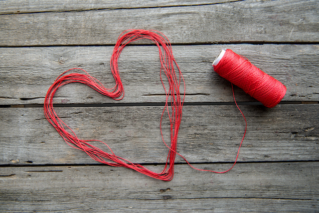 Heart sign made from red thread on wooden surface