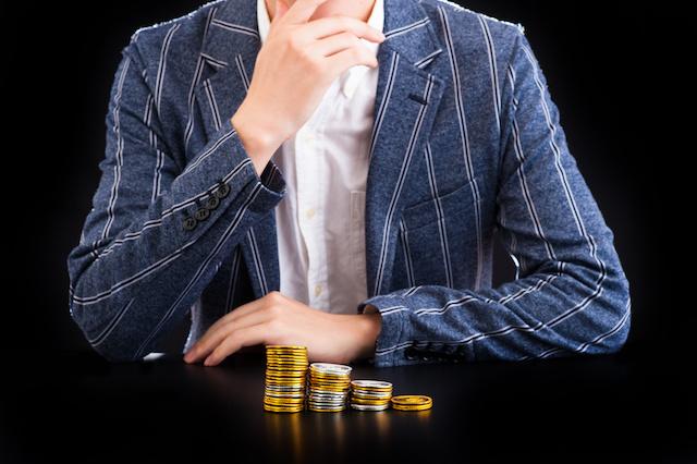 お金を積み上げる男性