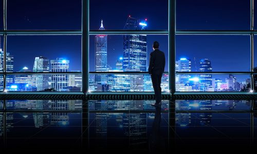 現象・成功Back view of thoughtful businessman looking out of big office window at office ,planning future project concept,night scene .
