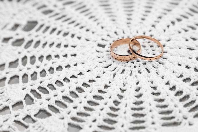 Wedding rings on white lace background