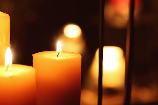 Beautiful burning candles in darkness, closeup