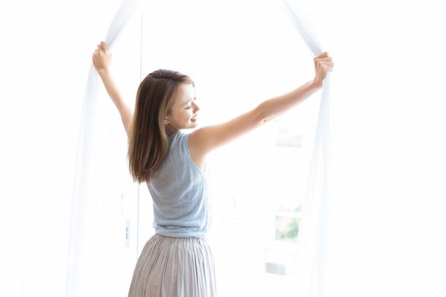 現象・カーテンを開ける女性