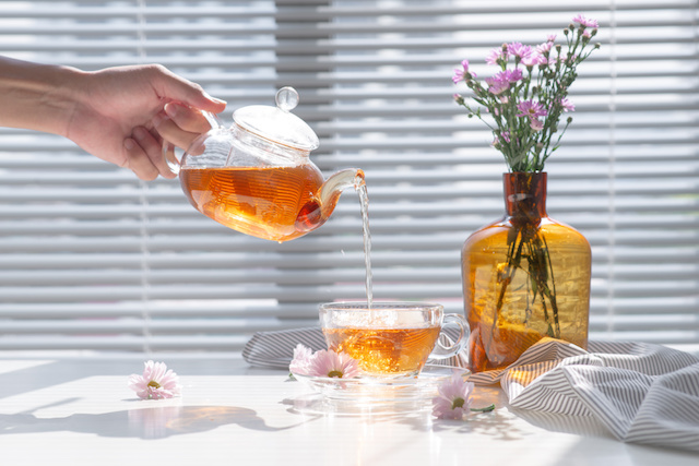 Tea being poured into glass teacup in the morning.