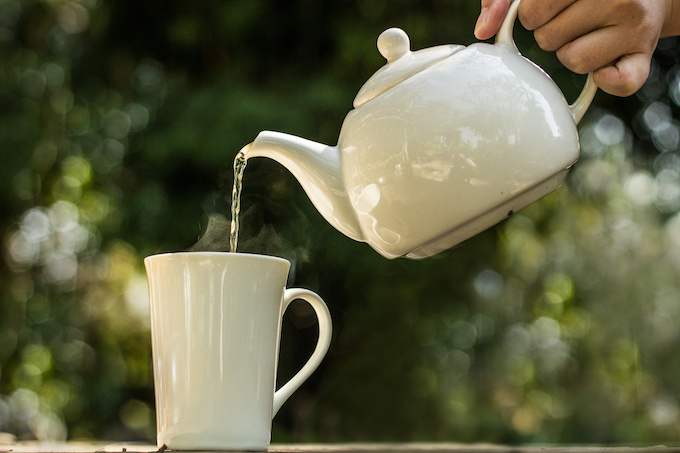 Woman hand rinses the White ceramic teapot before brewing the hot tea in to white cup with morning sunlight