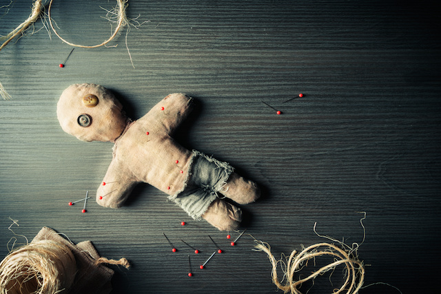 Voodoo doll with dramatic lighting on a wooden background