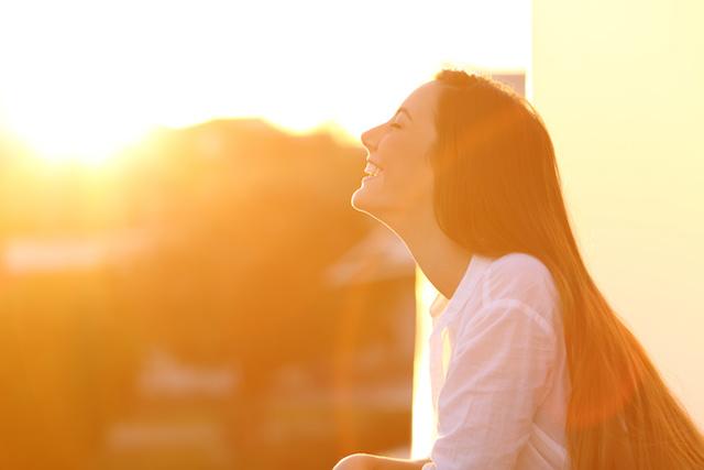 現象・夕日を浴びる女性Woman breathing at sunset in a balcony