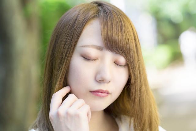 目を閉じて考える若い女性