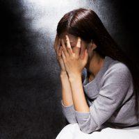 現象・絶望、顔を覆う女性