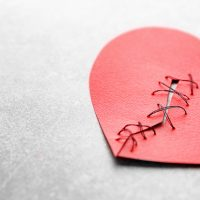 愛・復活愛Paper heart cut in half and sewn back together on light background. Relationship problems