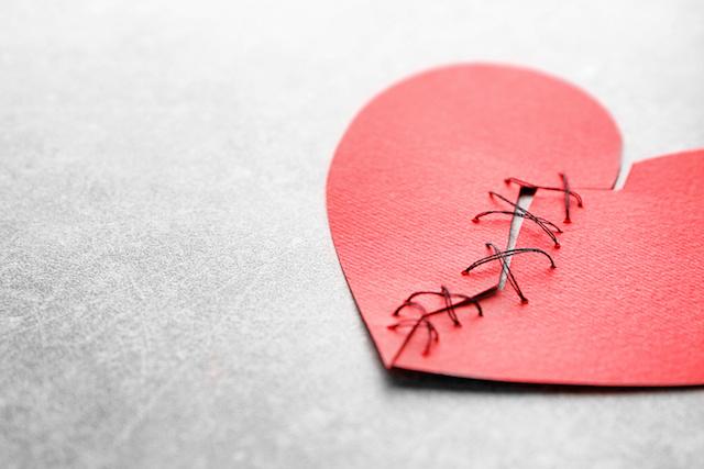 愛・復活愛Paper heart cut in half and sewn back together on light background. Relationship problems