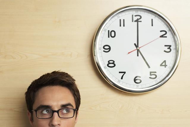 目線より上の時計を見る男性