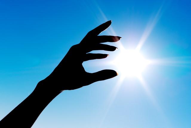 太陽と女性の手