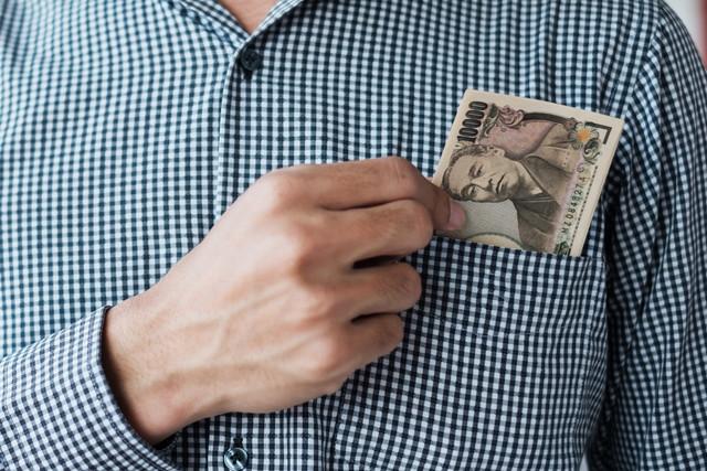 胸ポケットに1万円札を入れる男性