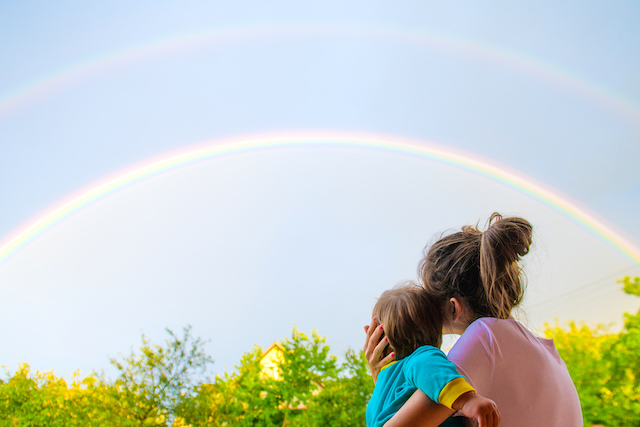 二重の虹を見る親子