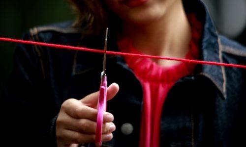 赤い糸を切る女性
